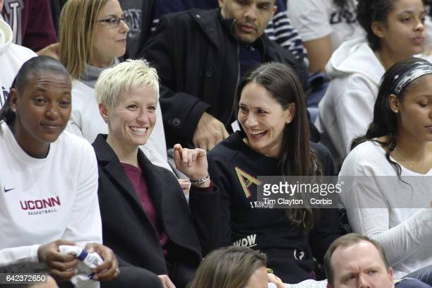United States soccer player Megan Rapinoe with former UConn basketball players Sue Bird and Maya Moore watching the UConn side as they go for their...