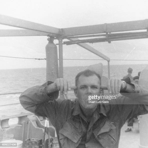 A United States soldier sticks his tongue out and makes a funny face while posing aboard a large ship Vietnam 1966