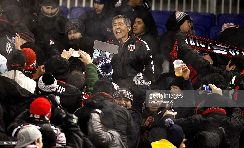 D.C. United team owner Will Chang cheers from the upper deck with fans after their Eastern Conference Semifinal match against the New York Red Bulls was postponed due to weather conditions at Red Bull Arena on November 7, 2012 in Harrison, New Jersey.