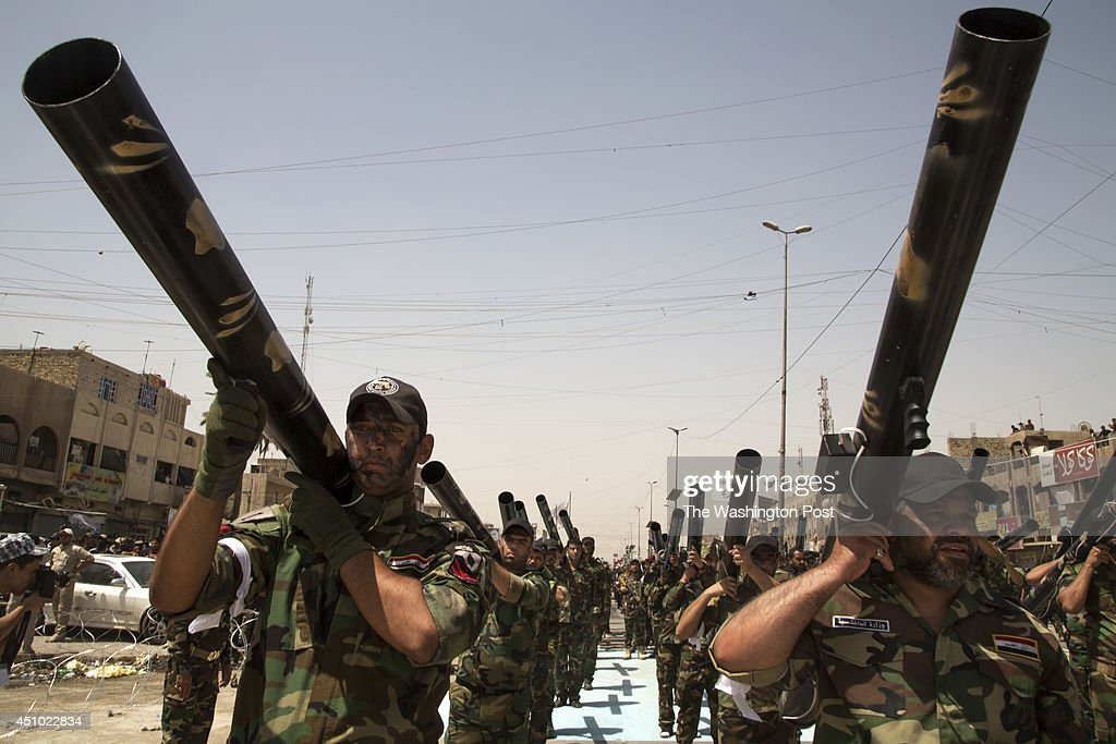 Units of Moqtada Sadr's militia parade down a main street of the Shi'a stronghold of Sadr City June 21 2014 in Eastern Baghdad Tens of thousands of...