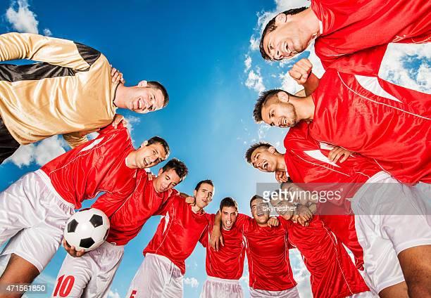 Unità di squadra di calcio contro il cielo azzurro.