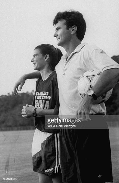 Univ of NC soccer coach Anson Dorrance w his arm around star player allAmerican forward Mia Hamm as he holds ball during practice on the Univ's...