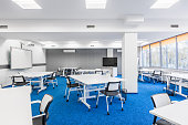 Modern university group study room with white desks and chairs