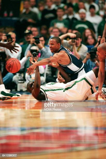 University of Arizona guard Jason Gardner and Michigan State center Zach Randolph battle for control of a loose ball during the Division 1 semifinal...