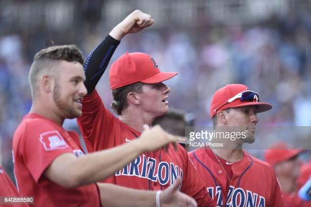 University of Arizona players signal to fans against Coastal Carolina University during the Division I Men's Baseball Championship held at TD...
