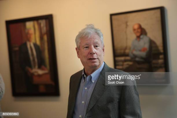 University of Chicago Professor Richard Thaler walks past portraits of previous Nobel winners as he arrives at his office after learning he had been...