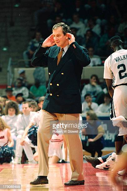 University of Connecticut basketball coach Jim Calhoun holds his hands to his ears on the sidelines during a game Hartford Connecticut 1989