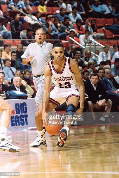 University of Connecticut basketball player Chris Smith dribbles the ball between his legs on the court during a game Hartford Connecticut 1995