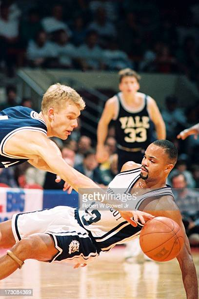 University of Connecticut basketball player Chris Smith falls to the court as he is fouled during a game against Yale Hartford Connecticut 1995