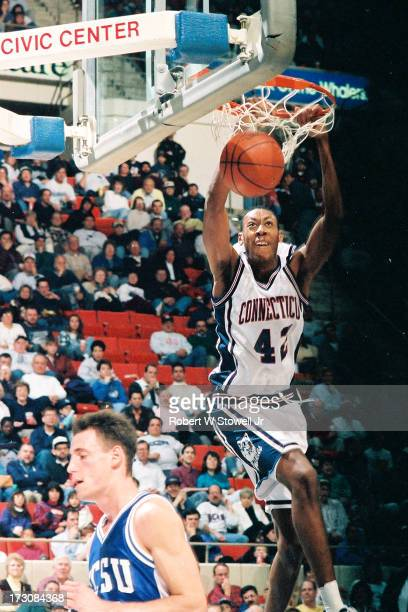 University of Connecticut basketball player Donyell Marshall hangs from the hoop during a game Hartford Connecticut 1994
