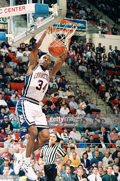 University of Connecticut basketball player Ray Allen hangs from the hoop during a game Hartford Connecticut 1994