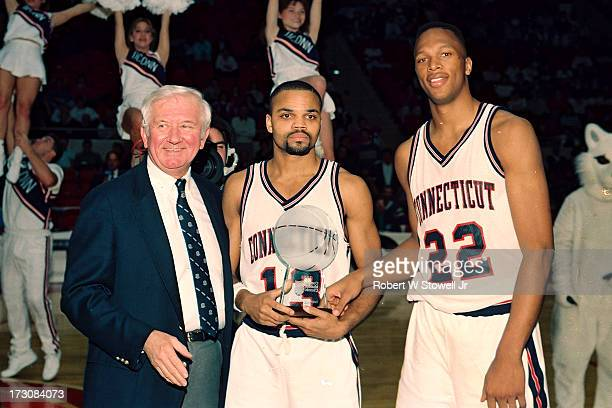 University of Connecticut basketball players Chris Smith and Rod Sellers accept the Connecticut Mutual Classic championship trophy from CEO Dennis...