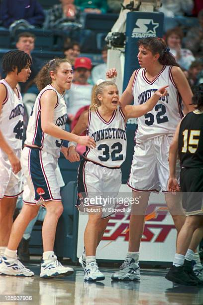 University of Connecticut's basketball player Pam Webber number 32 gestures with emotion as teammates Carla Berube and Kara Wolters stand beside her...