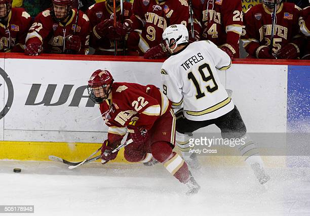 University of Denver Pioneers forward Logan O'Connor battles for control of the puck against Western Michigan Broncos forward Frederik Tiffels along...