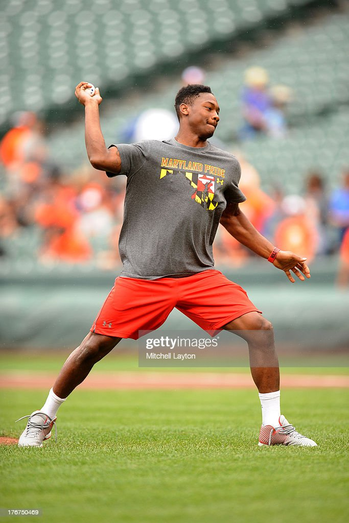 University of Maryland football player Stefon Diggs throws out the first pitch before a baseball game between the Baltimore Orioles and the Colorado Rockies on August 18, 2013 at Oriole Park at Camden Yards in Baltimore, Maryland.