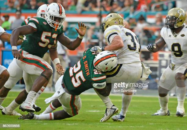 University of Miami defensive back Derrick Smith tackles Aback Nathan Cottrell during an NCAA football game between the Georgia Tech Yellow Jackets...