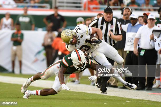 University of Miami defensive back Jaquan Johnson tackles Georgia Tech Aback Nathan Cottrell during an NCAA football game between the Georgia Tech...