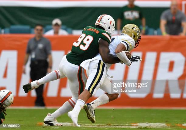 University of Miami defensive lineman Joe Jackson tackles Georgia Tech wide receiver Ricky Jeune during an NCAA football game between the Georgia...