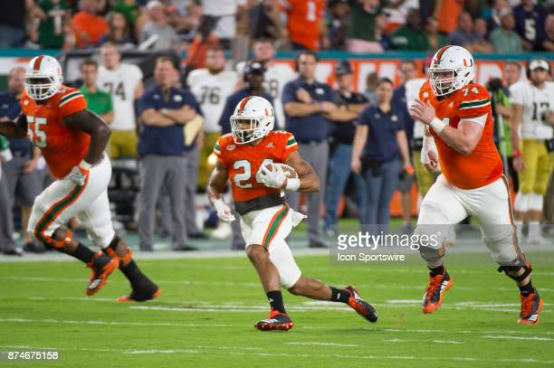 University of Miami Hurricanes Running Back Travis Homer runs with the ball along with University of Miami Hurricanes Offensive Lineman Tyler...