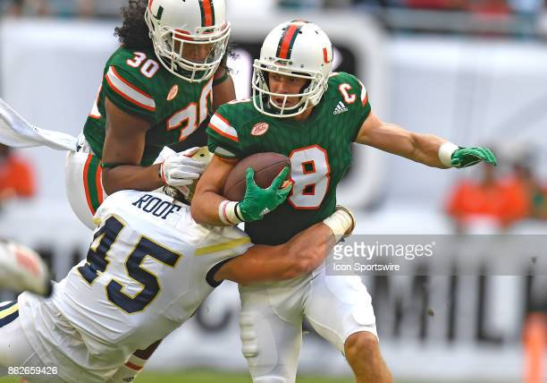 University of Miami wide receiver Braxton Berrios is tackled by Georgia Tech linebacker TD Roof during an NCAA football game between the Georgia Tech...