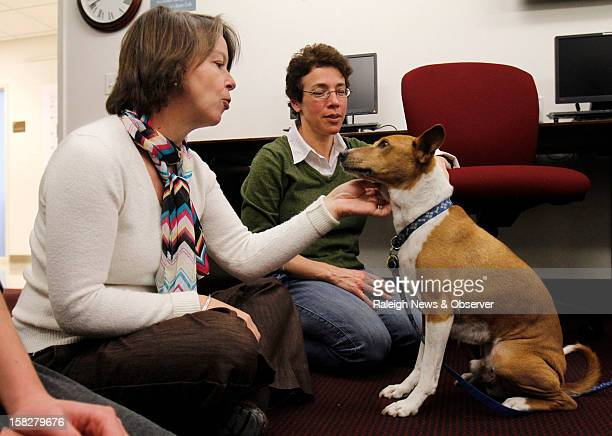 University of North Carolina Journalism school staffer Rachel Pittman left plays with Mickey an 11 year old basenji as Mickey's owner Emily Silverman...