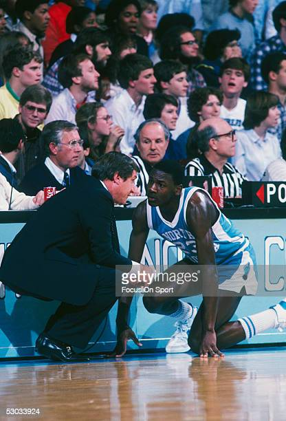 University of North Carolina's Michael Jordan talks to head coach Dean Smith during a game circa 1980's