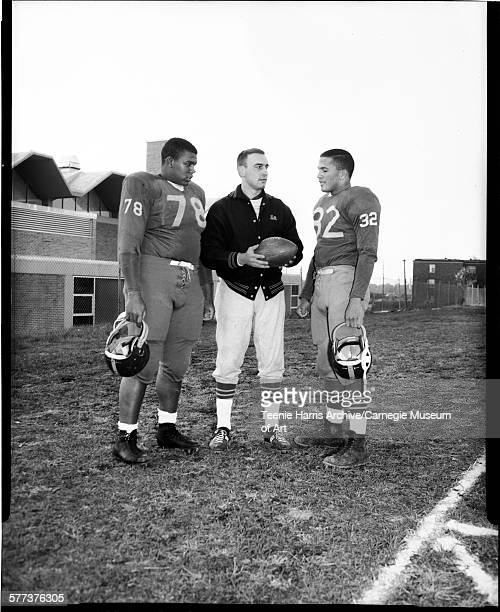 University of Pittsburgh football players no 78 James Jones and no 32 Eric Crabtree standing on either side of freshmen football coach Bill Kaliden...