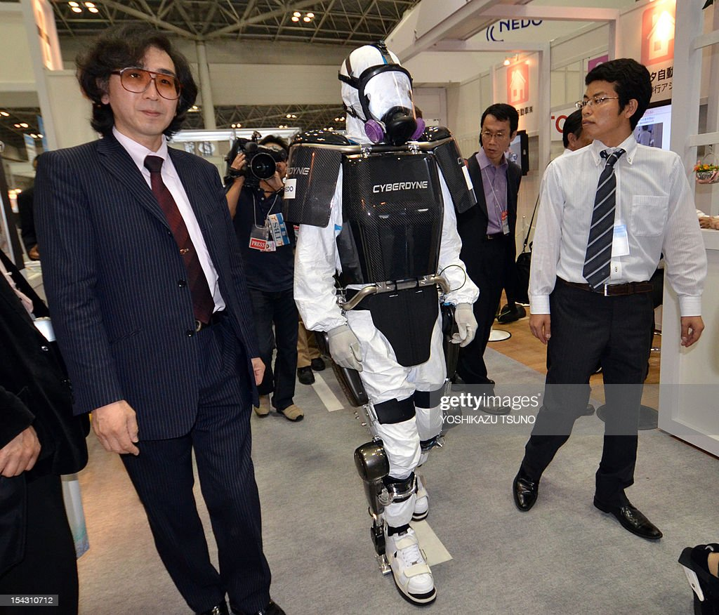 University of Tsukuba professor and president of Cyberdyne Yoshiyuki Sankai (L) unveils a robot suit entitled HAL (Hybrid Assistive Limb) at the Japan Robot Week exhibition in Tokyo on October 18, 2012. The new type of robot suits are to be used by workers at nuclear disaster sites and will be field tested at TEPCO's Fukushima power plant. AFP PHPOTO / Yoshikazu TSUNO