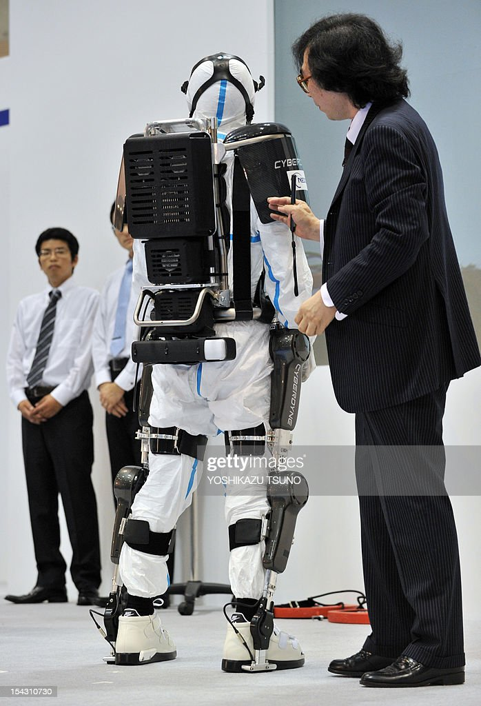 University of Tsukuba professor and president of Cyberdyne Yoshiyuki Sankai (R) unveils a robot suit entitled HAL (Hybrid Assistive Limb) at the Japan Robot Week exhibition in Tokyo on October 18, 2012. The new type of robot suits are to be used by workers at nuclear disaster sites and will be field tested at TEPCO's Fukushima power plant. AFP PHPOTO / Yoshikazu TSUNO