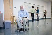 University professor in a wheelchair with his students in the background