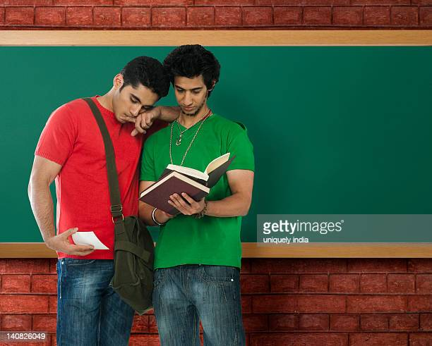 University student looking at a photograph beside his friend in a classroom