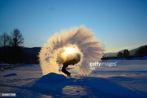 A university student of Jilin Agricultural University splashes water to the air while it freezes to ice quickly on January 25 2016 in Changchun Jilin...