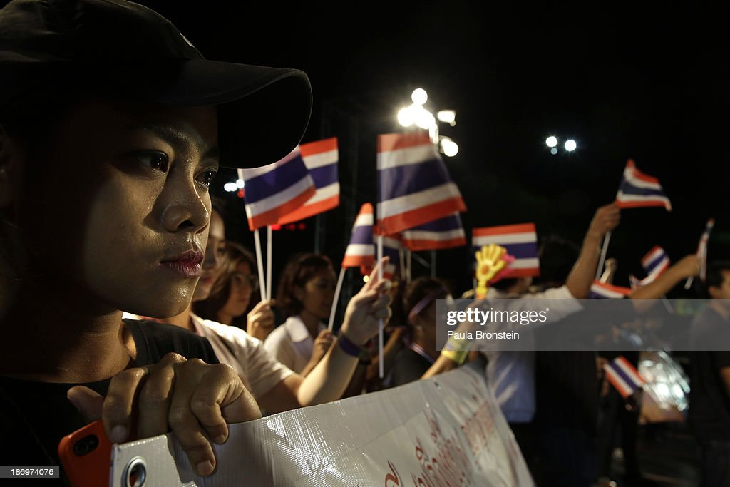 University student protestors wave Thai flags during rally against a controversial amnesty bill that passed in Parliament last week on November 5, 2013 in Bangkok, Thailand. Thousands attended various protests around the capitol city organized by the opposition Democrat Party. If the law goes into effect it will whitewash all crimes against the billionaire, former leader Thaksin Shinawatra setting the stage for him to return to Thailand.