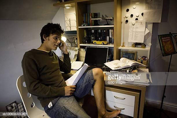 University student sitting at desk, talking on phone