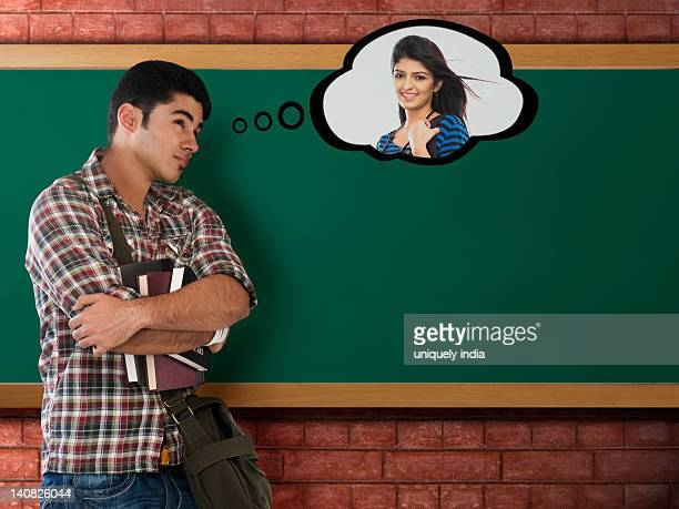 University student thinking of his girlfriend in a classroom