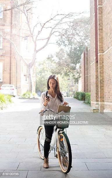 University student using mobile phone on bike