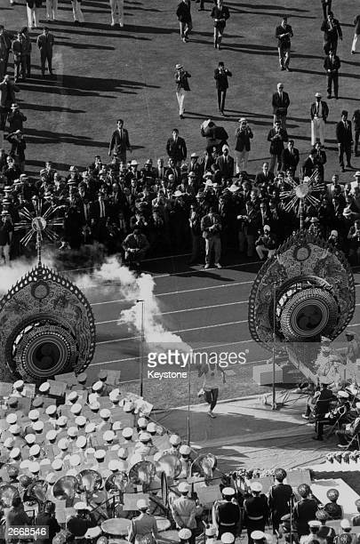 University student Yoshinori Sakai carrying the Olympic torch as he runs between the 'flame drums' and past the band in the Tokyo National Stadium at...