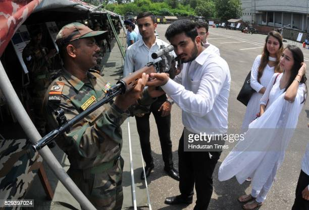 University students are given a description of instruments and weapons used by the Indian Army during an exhibition at Jammu University on August 10...