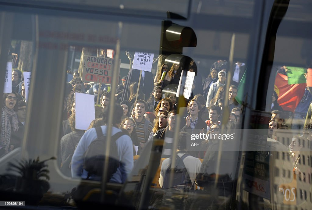 University students are reflected in the glass of a bus as they protest against the Portuguese government's austerity cuts and education benefits in Lisbon on November 22, 2012.