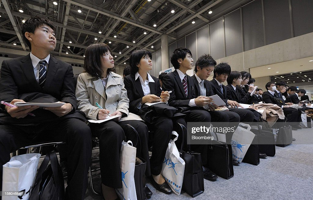 University students attend a presentation at a job fair hosted by Mynavi Corp. in Tokyo, Japan, on Saturday, Dec. 8, 2012. In Japan, many students accept job offers from large companies six months before graduating and may stay with the same employer until retirement, said Yoshihide Suzuki, an administrative director at the career center at Waseda University. Photographer: Akio Kon/Bloomberg via Getty Images