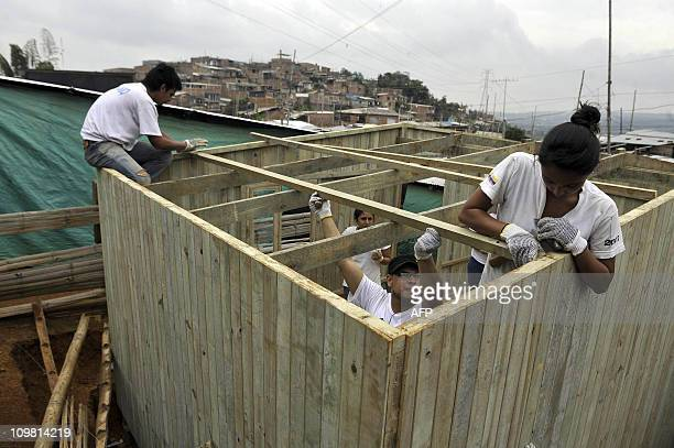 University students build a wooden house for a poor family in El Arbol neighborhood in the outskirts of Cali deparment of Valle del Cauca Colombia on...