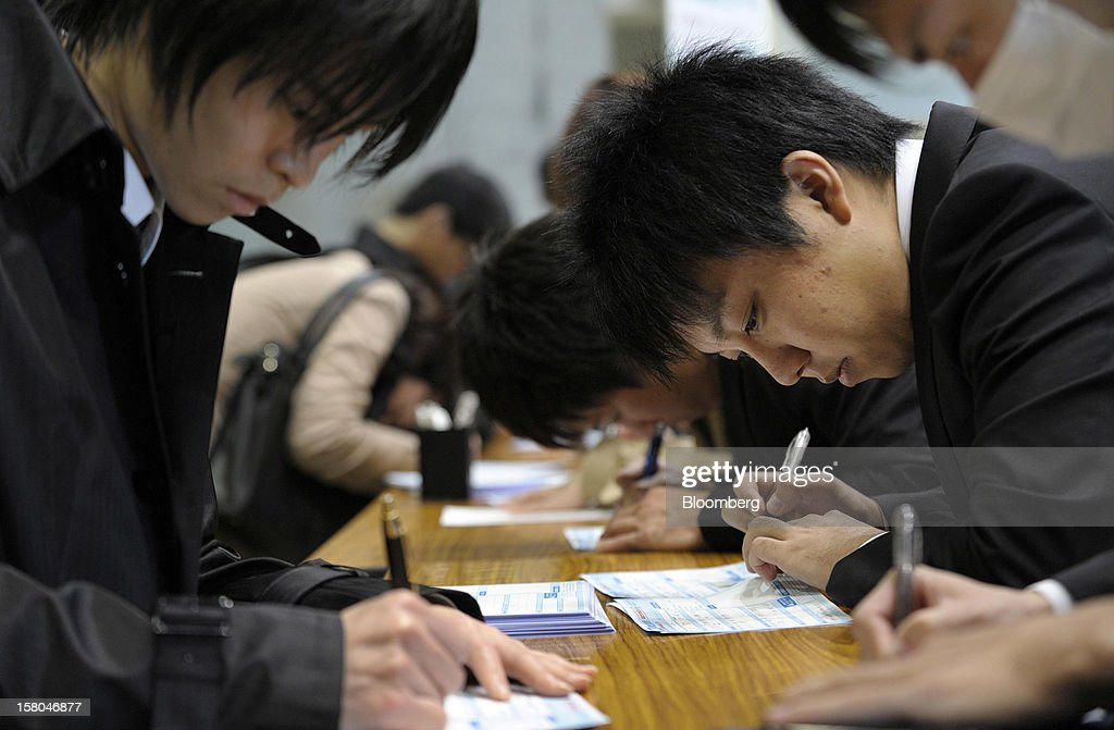 University students fill out application forms at a job fair hosted by Mynavi Corp. in Tokyo, Japan, on Saturday, Dec. 8, 2012. In Japan, many students accept job offers from large companies six months before graduating and may stay with the same employer until retirement, said Yoshihide Suzuki, an administrative director at the career center at Waseda University. Photographer: Akio Kon/Bloomberg via Getty Images
