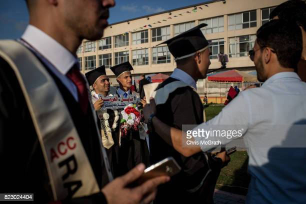 University students from AlAzhar University celebrate and pose for photos ahead of the start of their graduation ceremony on July 18 2017 in Gaza...