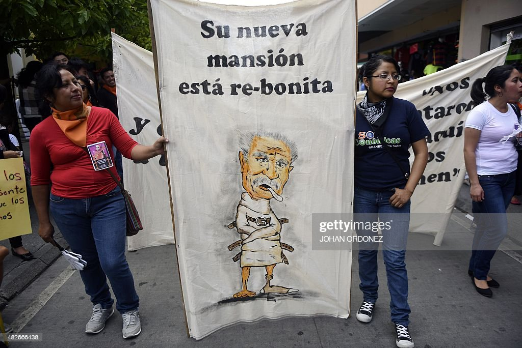 University students hold a sign depicting former Guatemalan dictator Jose Efrain Rios Montt during a demonstration demanding the resignation of...