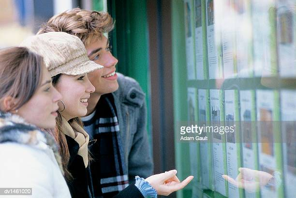 University Students Looking at an Estate Agent's Window Display
