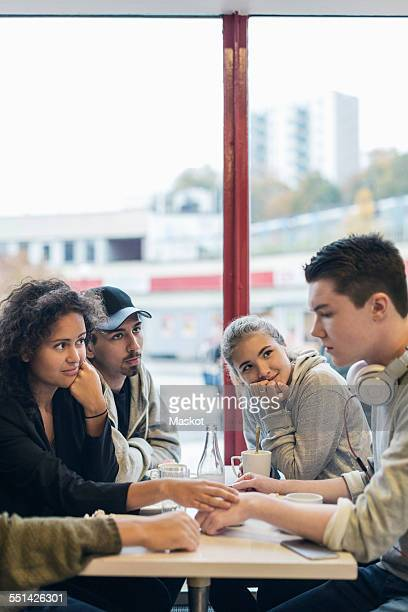 University students looking at sad friend in cafe