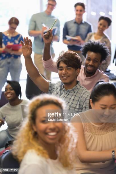 University students raising hands at IT seminar