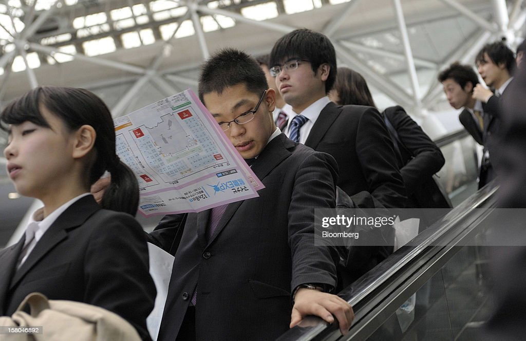 University students ride an escalator at a job fair hosted by Mynavi Corp. in Tokyo, Japan, on Saturday, Dec. 8, 2012. In Japan, many students accept job offers from large companies six months before graduating and may stay with the same employer until retirement, said Yoshihide Suzuki, an administrative director at the career center at Waseda University. Photographer: Akio Kon/Bloomberg via Getty Images