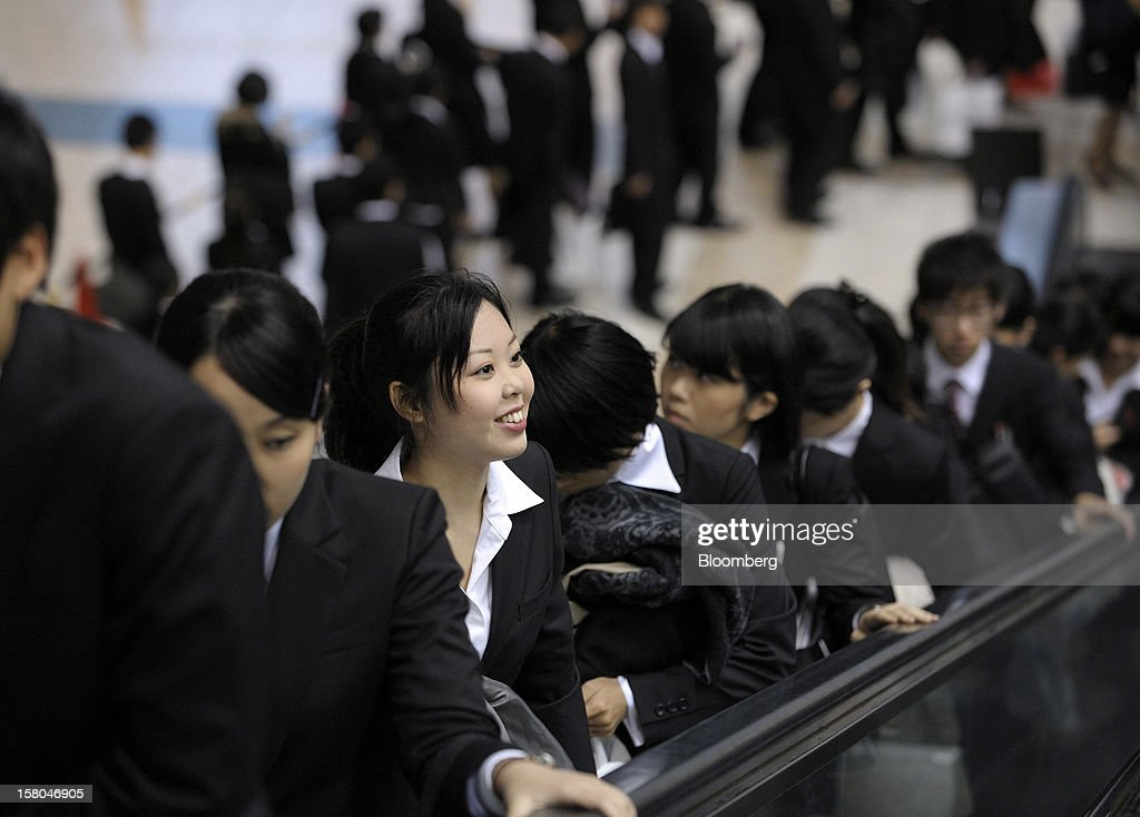 University students ride on an escalator at a job fair hosted by Mynavi Corp. in Tokyo, Japan, on Saturday, Dec. 8, 2012. In Japan, many students accept job offers from large companies six months before graduating and may stay with the same employer until retirement, said Yoshihide Suzuki, an administrative director at the career center at Waseda University. Photographer: Akio Kon/Bloomberg via Getty Images