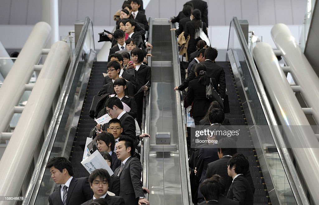 University students ride on escalators at a job fair hosted by Mynavi Corp. in Tokyo, Japan, on Saturday, Dec. 8, 2012. In Japan, many students accept job offers from large companies six months before graduating and may stay with the same employer until retirement, said Yoshihide Suzuki, an administrative director at the career center at Waseda University. Photographer: Akio Kon/Bloomberg via Getty Images